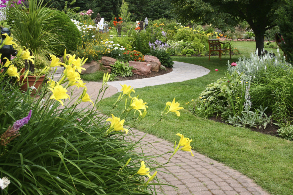 manicured garden with flowers, pathway and bench frontier landscaping